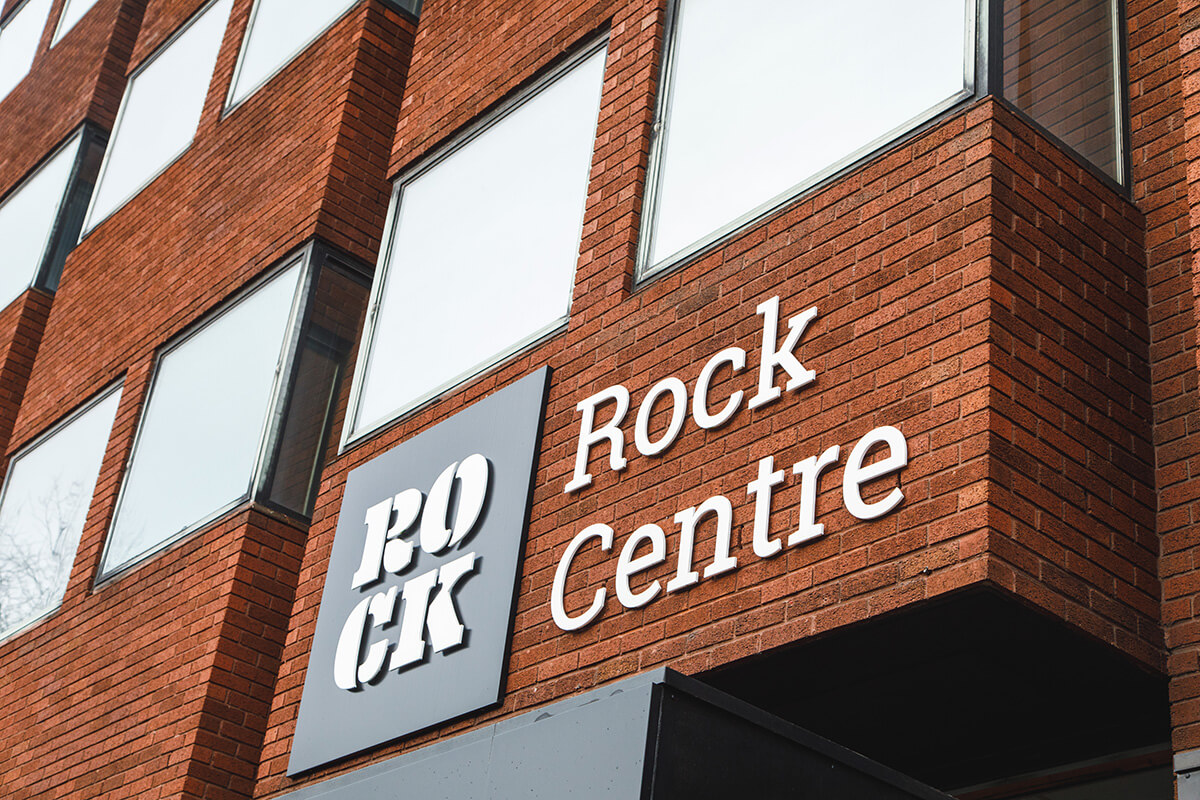 A brick office building with a sign saying The Rock Centre