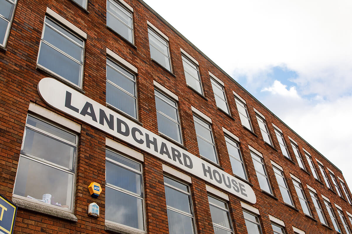 A picture of a brick office building with a larde sign saying Landchard House