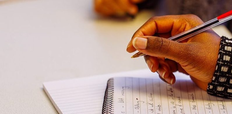 An image of a womans hand writing on a notepad during a training session