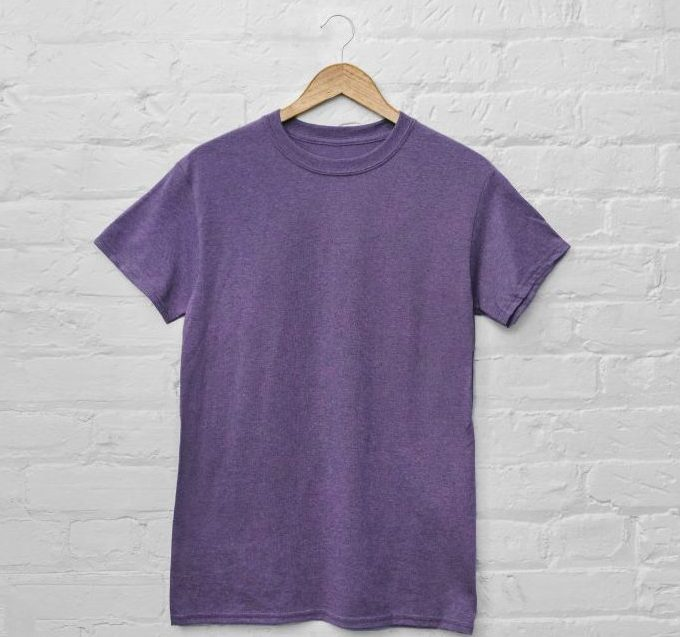 A picture of a purple t shirt hanging against a white wall