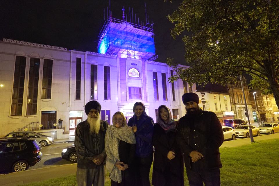 A group of people standing in front of a Gurdwara building lit with purple lights