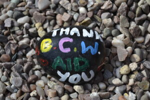 """A stone brightly painted with the words """"thank you BCWA"""""""